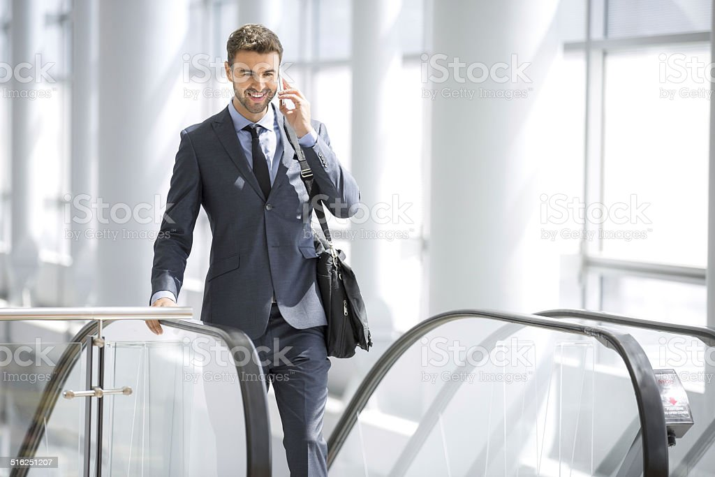 Businessman on the phone smiling at the escalator stock photo