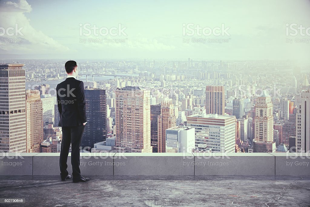 Businessman on the roof and looking at the city stock photo