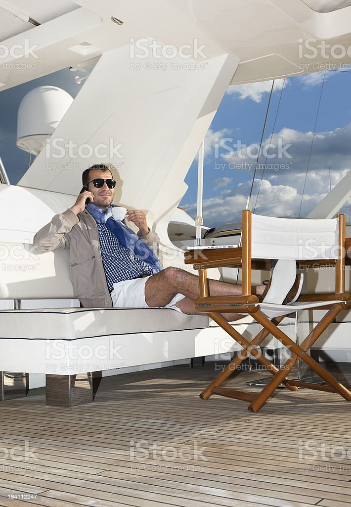 Businessman on the yacht drinking coffee and relaxing royalty-free stock photo