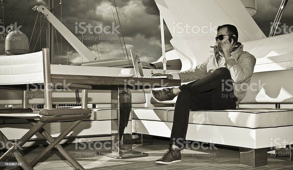 Businessman on the yacht. Phone discussion and reading e-mails. royalty-free stock photo