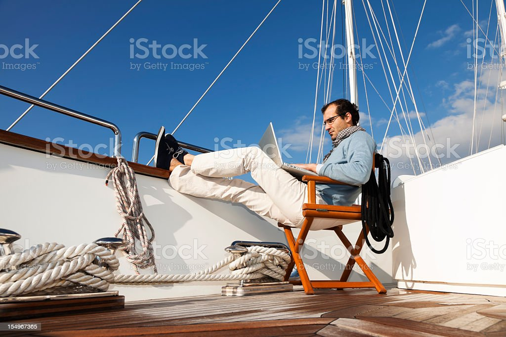 A businessman on the yacht texting and reading emails royalty-free stock photo