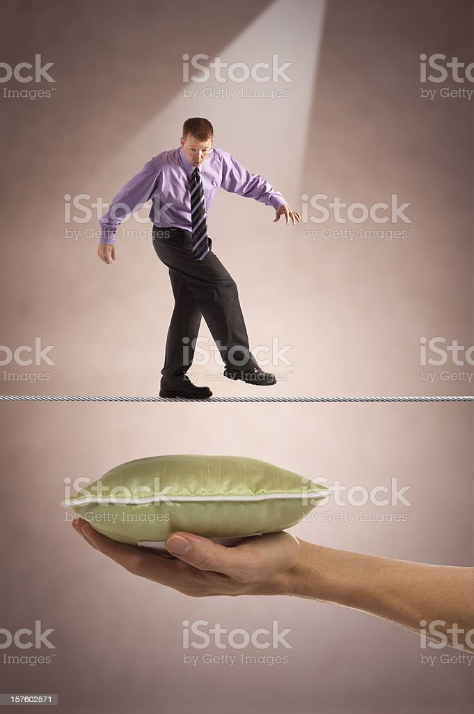 Businessman on tightrope with safety below royalty-free stock photo