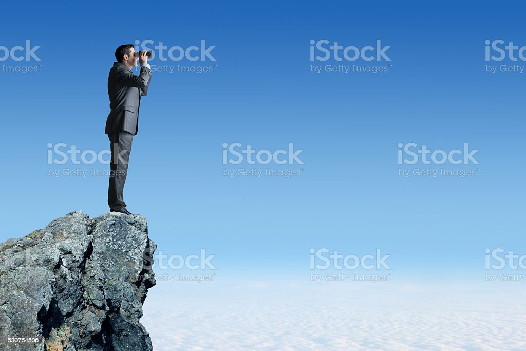 Businessman On Top Of Cliff Looking Through Binoculars stock photo