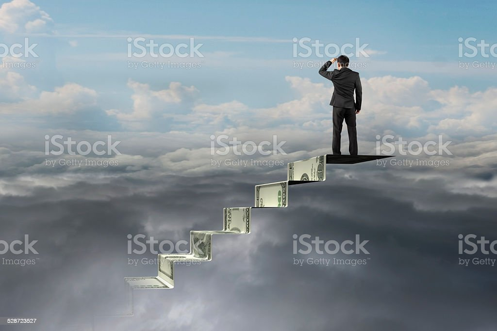 businessman on top of money stairs looking at natural cloudscape stock photo