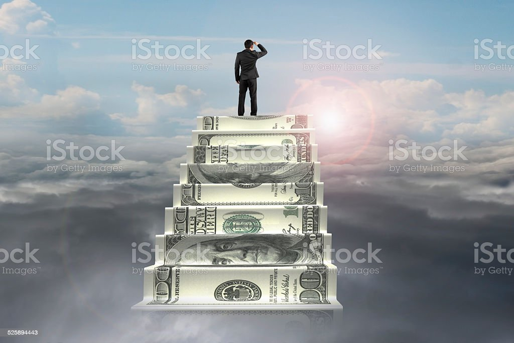 businessman on top of money stairs looking at sunlight cloudscap stock photo