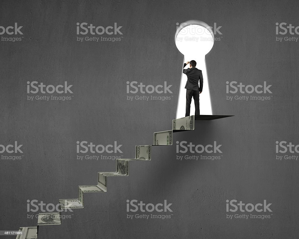 Businessman on top of money stairs with key hole stock photo