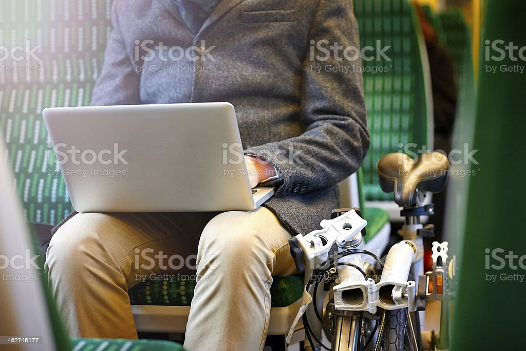 Businessman on train using laptop stock photo