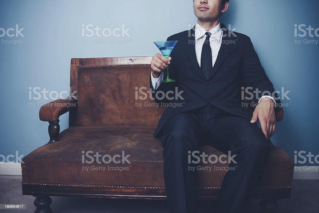 Businessman on vintage sofa drinking cocktail royalty-free stock photo
