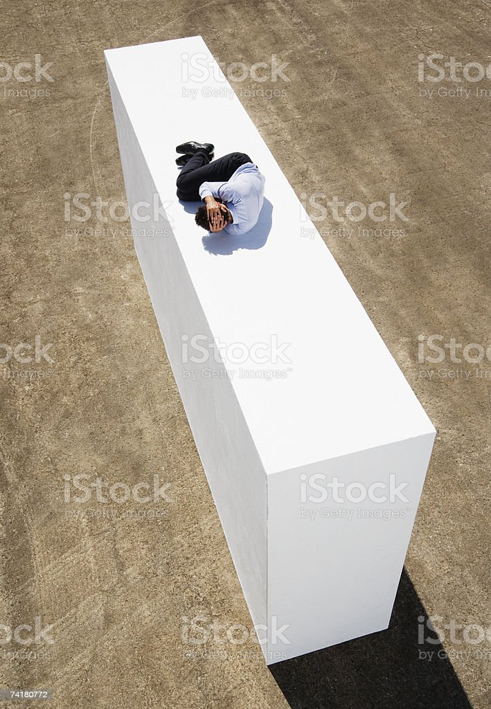 Businessman on wall outdoors in fetal position stock photo