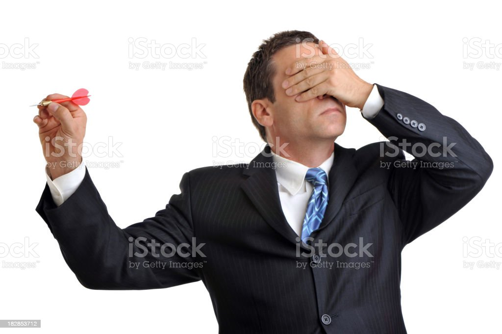 Businessman on white throwing dart with hand over eyes stock photo