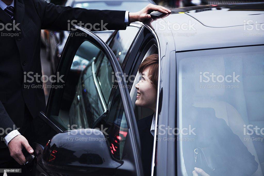 Businessman opening car door for businesswoman stock photo