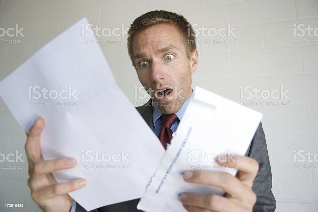 Businessman Opening Letter with Shocked Expression stock photo