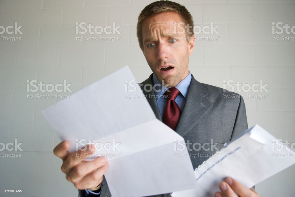 Businessman Opens Letter with Expression of Disbelief stock photo