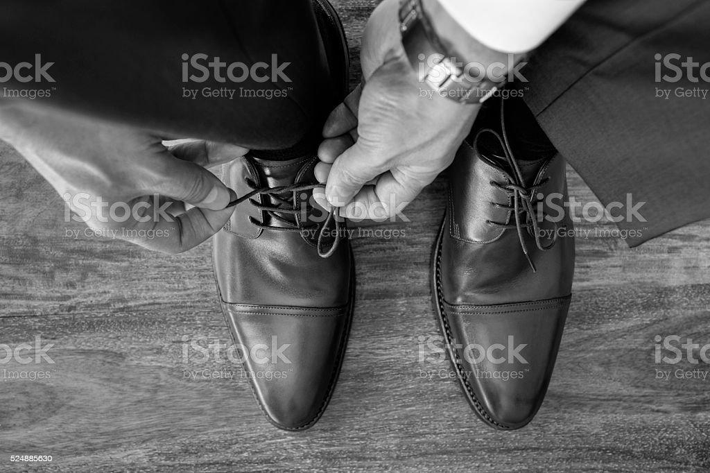 Businessman or groom tying shoe laces preparing stock photo