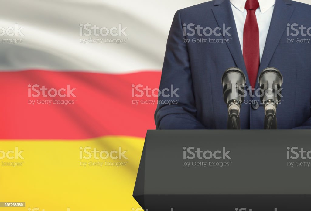 Businessman or politician making speech from behind a pulpit with national flag on background - South Ossetia stock photo