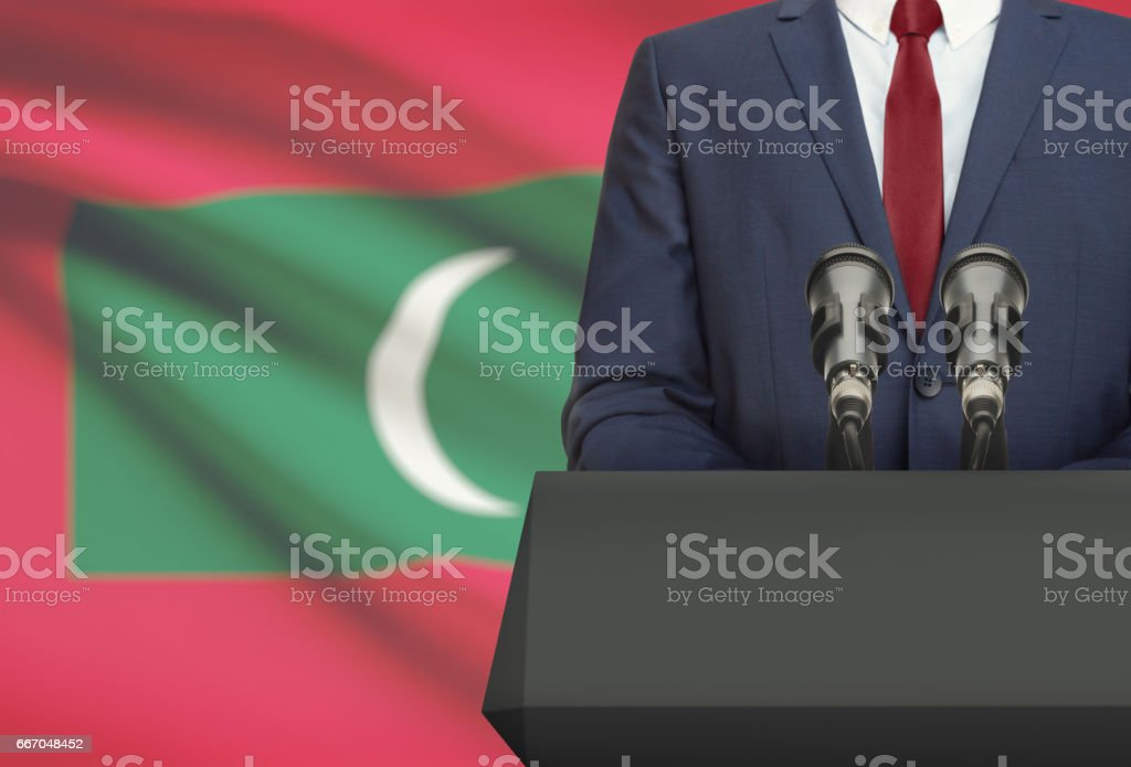 Businessman or politician making speech from behind a pulpit with national flag on background - Maldives stock photo