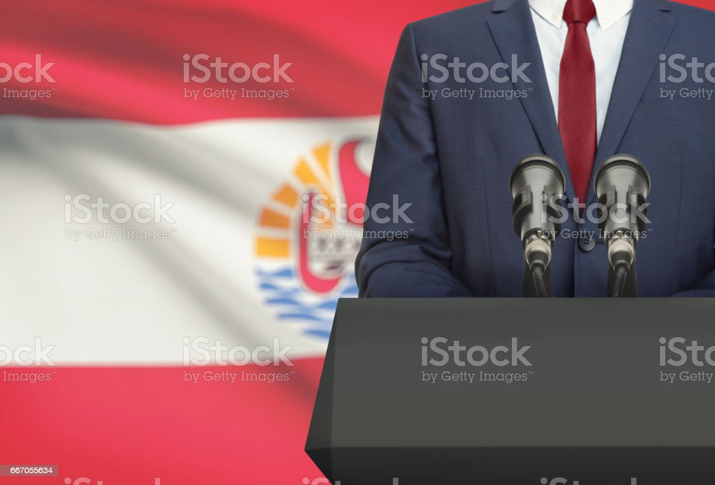 Businessman or politician making speech from behind a pulpit with national flag on background - French Polynesia stock photo