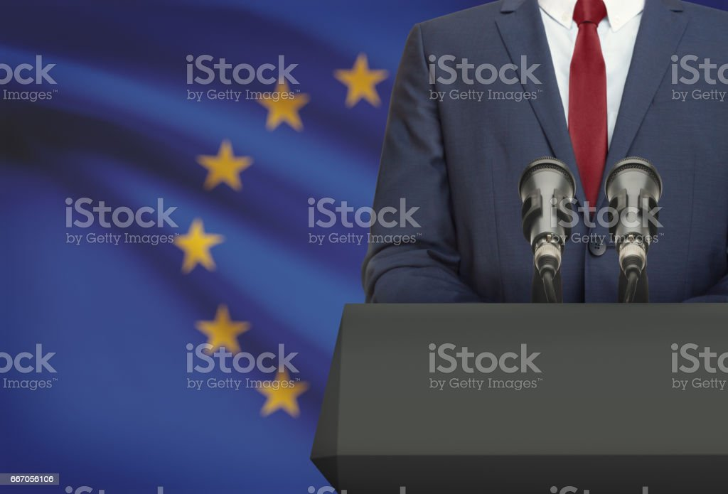 Businessman or politician making speech from behind a pulpit with national flag on background - European Union stock photo