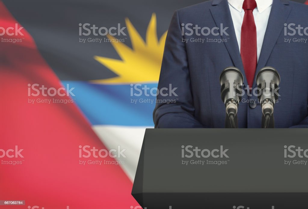 Businessman or politician making speech from behind a pulpit with national flag on background - Antigua and Barbuda stock photo
