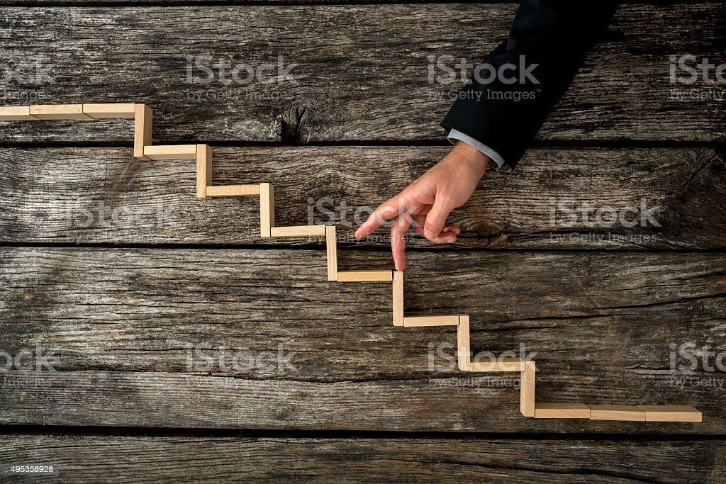 Businessman or student walking his fingers up wooden steps stock photo