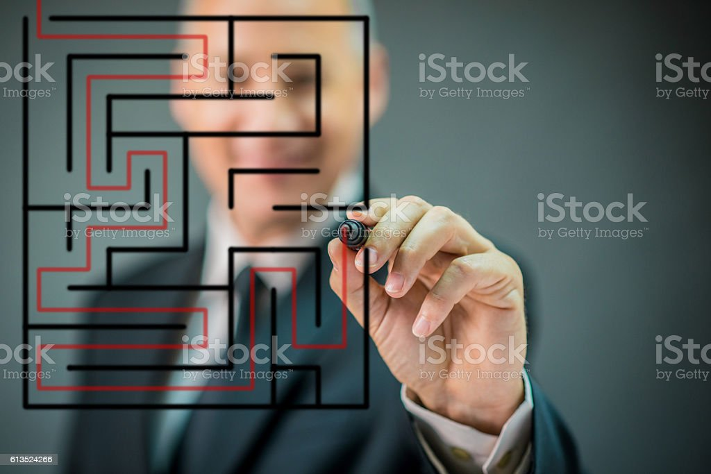 businessman or teacher with marker writing or drawing Labyrinth stock photo