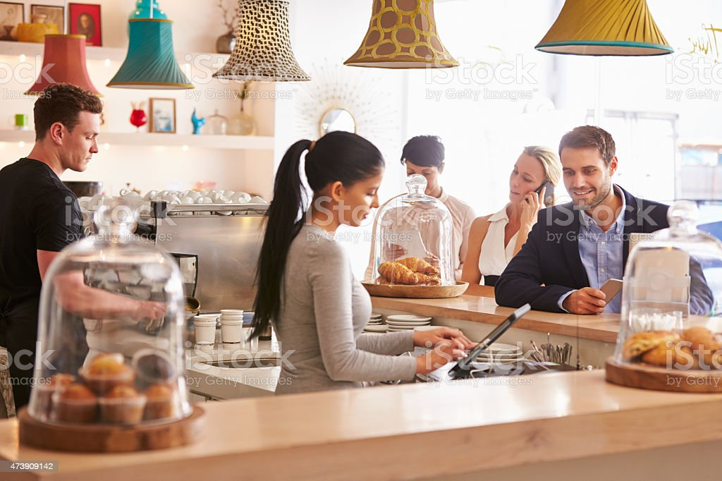 A businessman ordering at a counter in a cafe stock photo