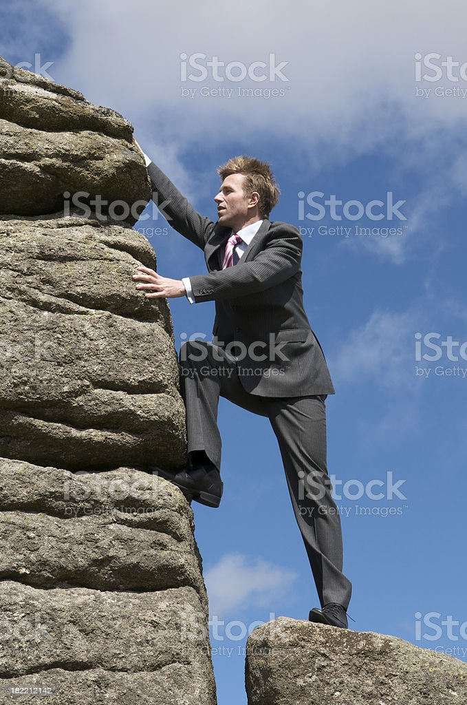Businessman Outdoors Climbing a Big Rock royalty-free stock photo