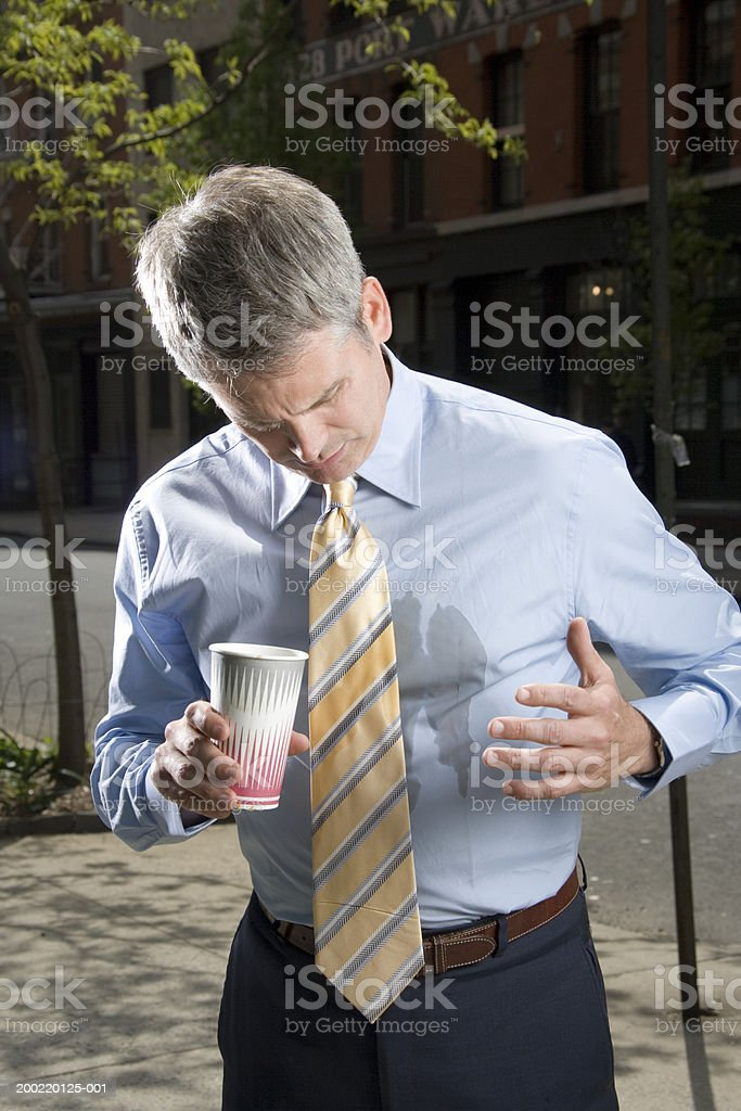 Businessman outdoors, coffee spilt on shirt stock photo
