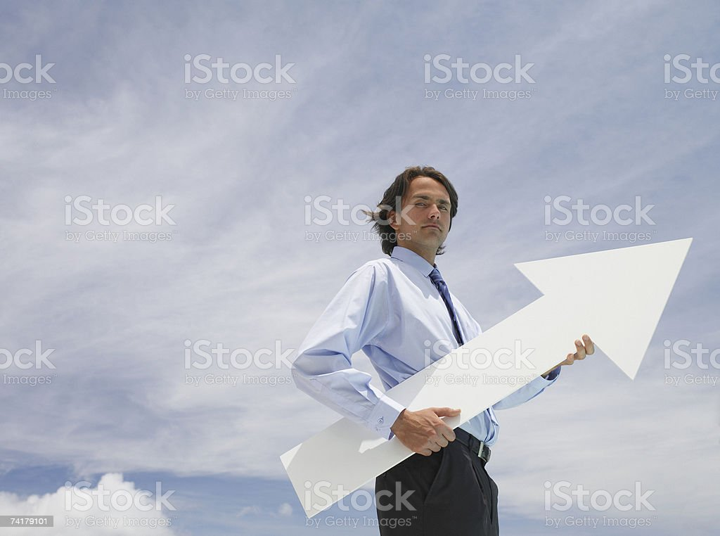 Businessman outdoors holding blank arrow with sky in background royalty-free stock photo