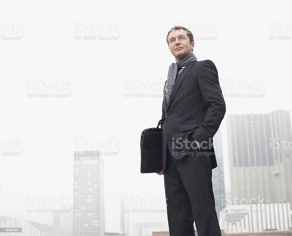Businessman outdoors holding briefcase royalty-free stock photo