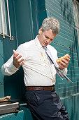 Businessman outdoors, hotdog sauces spilt on shirt