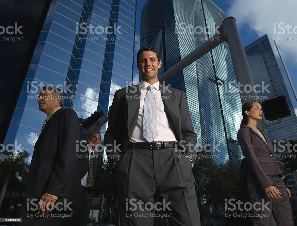 Businessman outdoors looking at camera with three businesspeople around him royalty-free stock photo