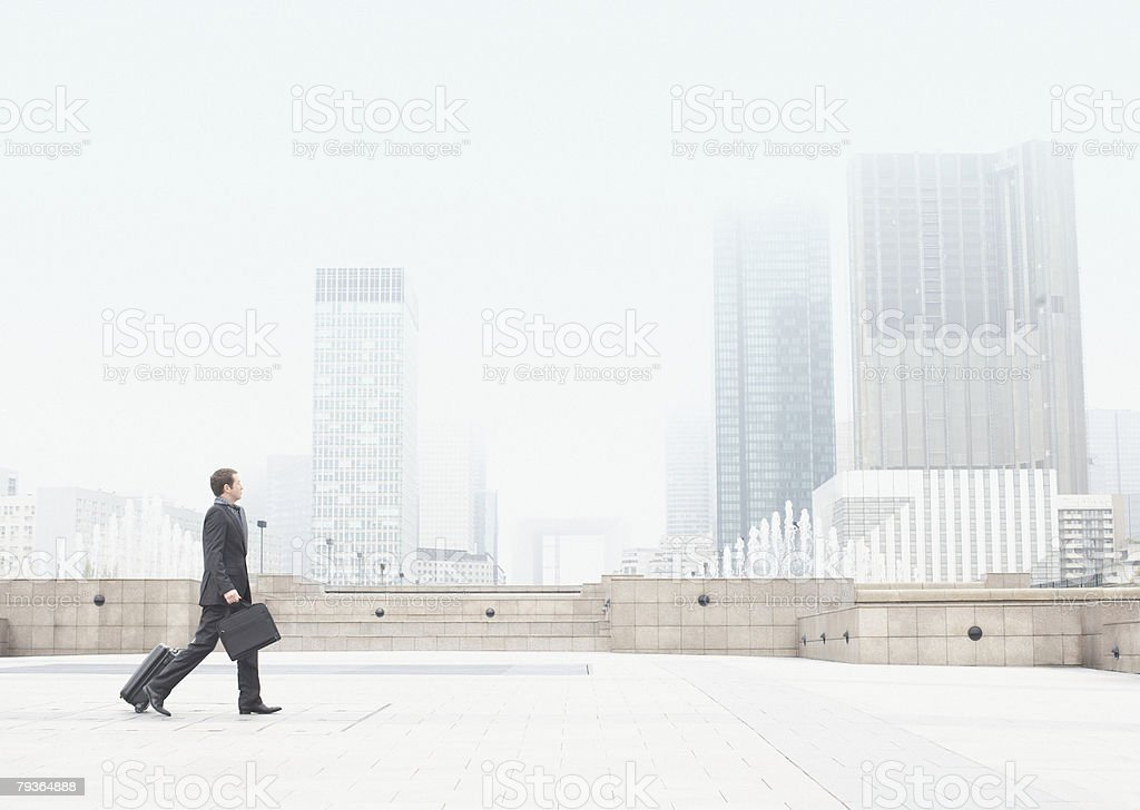 Businessman outdoors walking with luggage stock photo