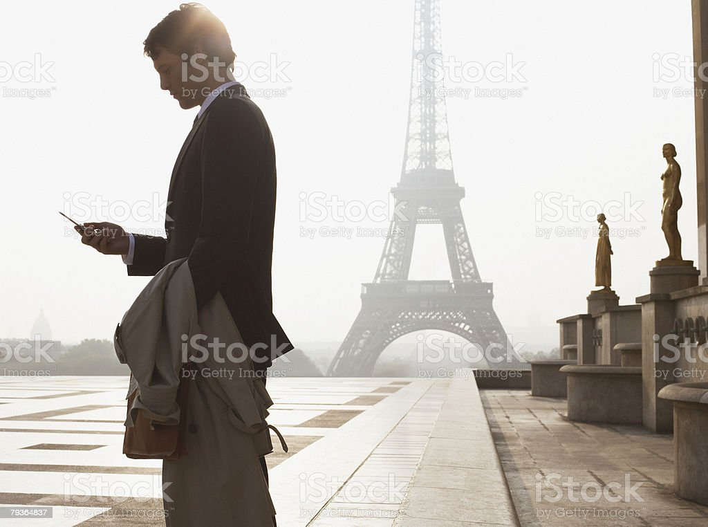 Businessman outdoors with cellular phone by Eiffel Tower stock photo