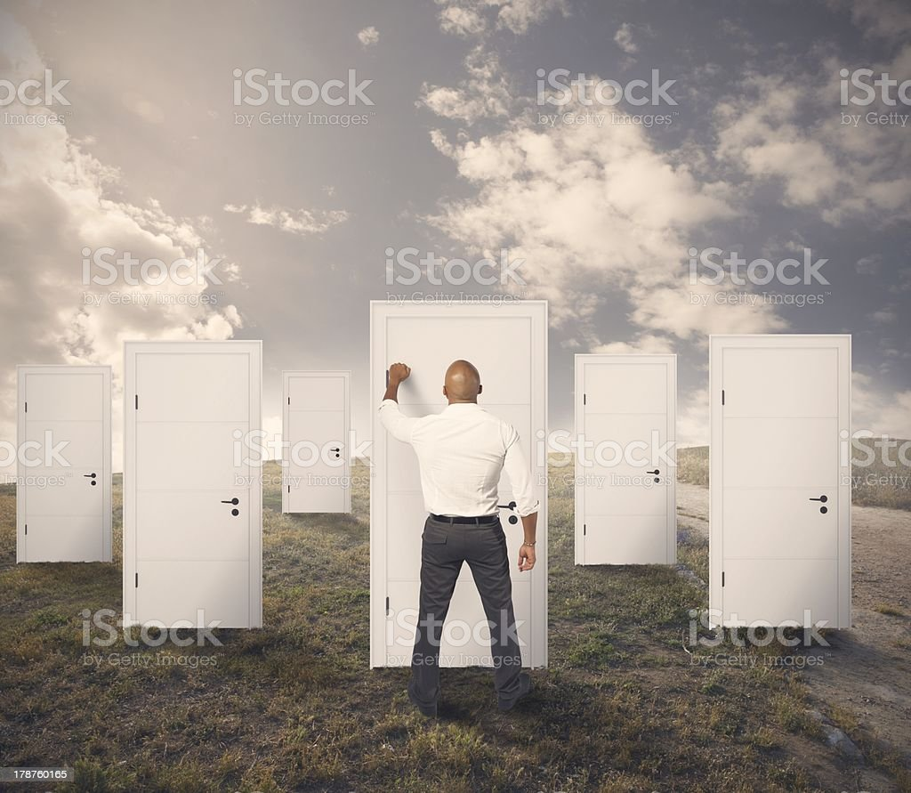 Businessman outside knocking on freestanding door stock photo