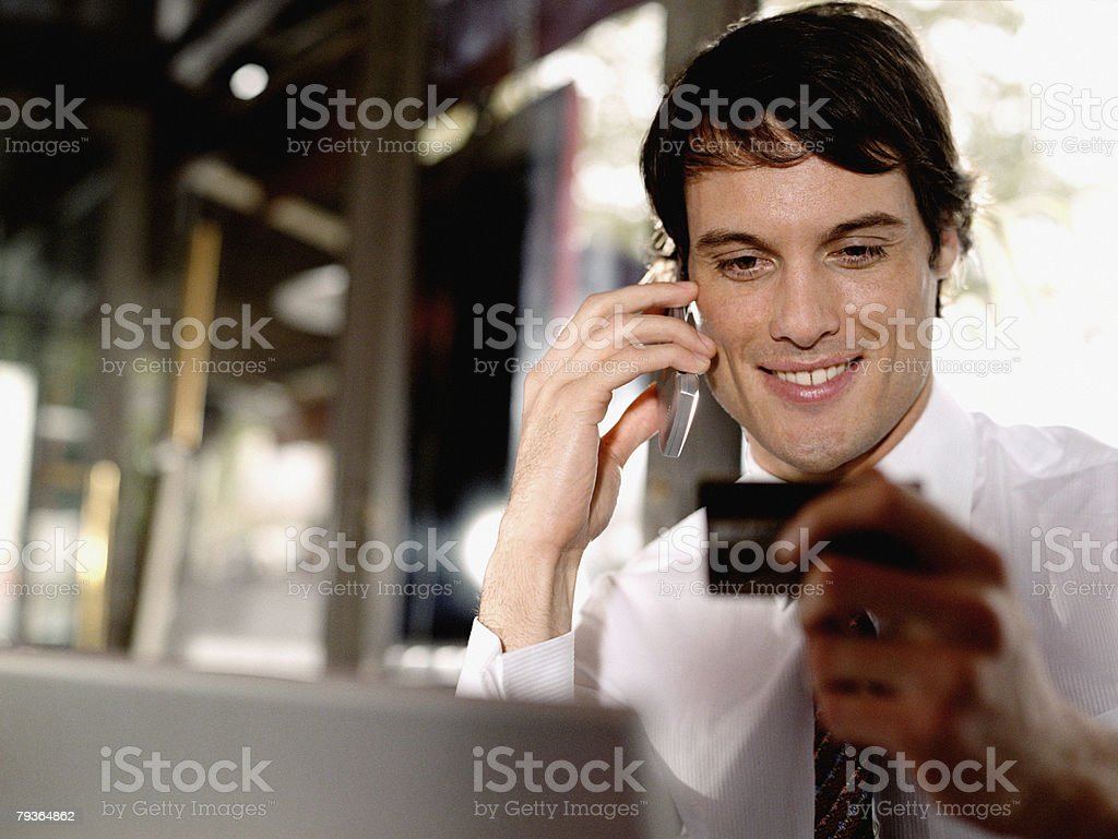 Businessman outside restaurant with credit card and mobile phone royalty-free stock photo