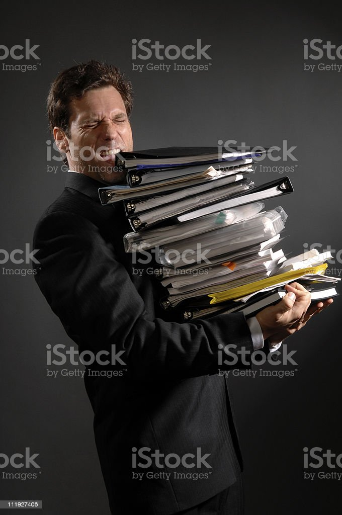 Businessman overloaded with Paperwork on Gray royalty-free stock photo