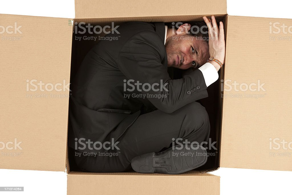 Businessman packed in a cardboard box stock photo