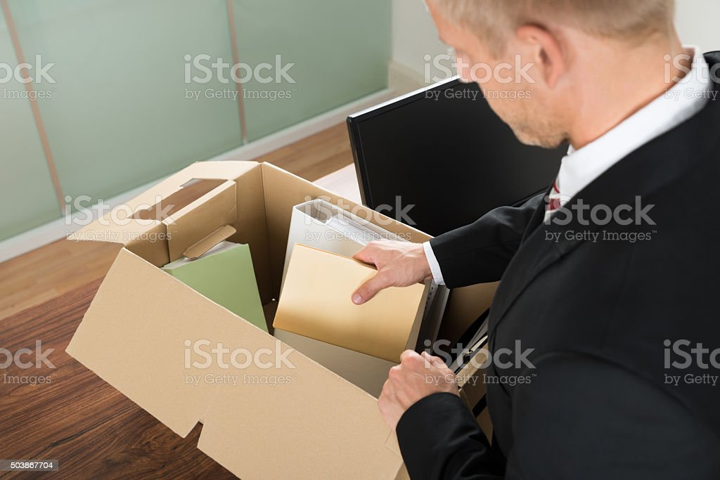 Businessman Packing Files In Cardboard Box stock photo