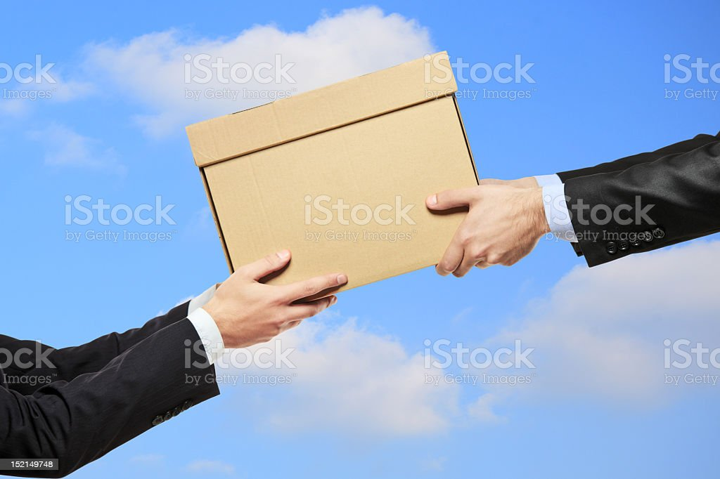 Businessman passing cardboard box to a colleague royalty-free stock photo
