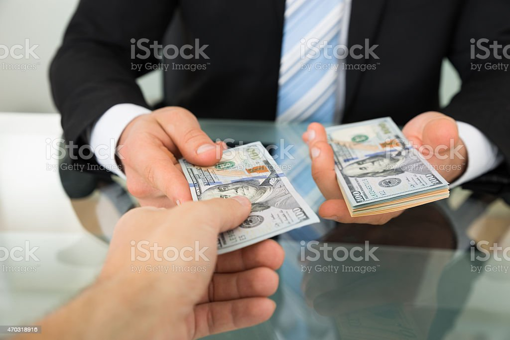 Businessman Passing Money To Colleague At Table stock photo