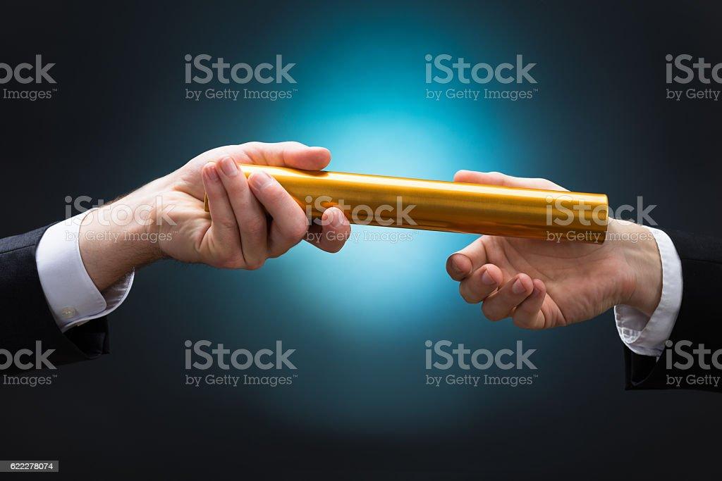 Businessman Passing Relay Baton To Colleague stock photo