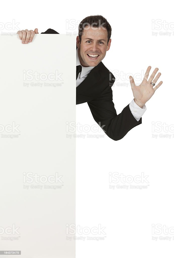 Businessman peeking behind from a placard stock photo