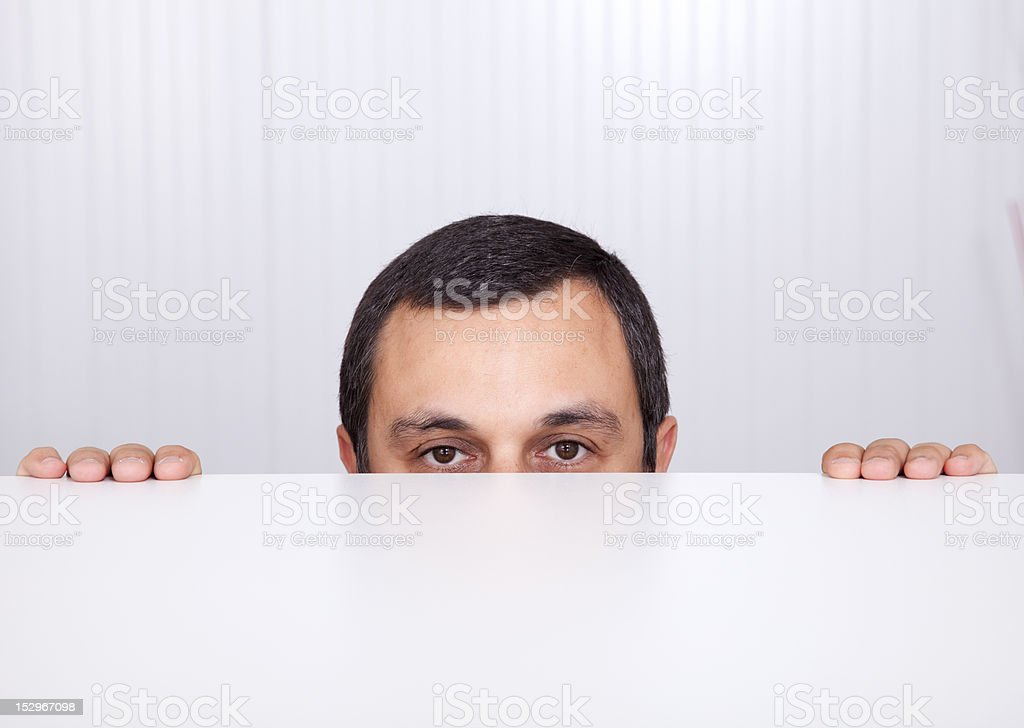 Businessman peeking behind the desk stock photo