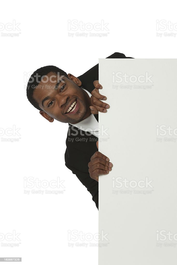 Businessman peeking from behind a placard royalty-free stock photo