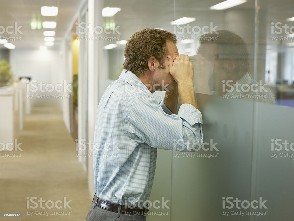 Businessman peering into conference room stock photo