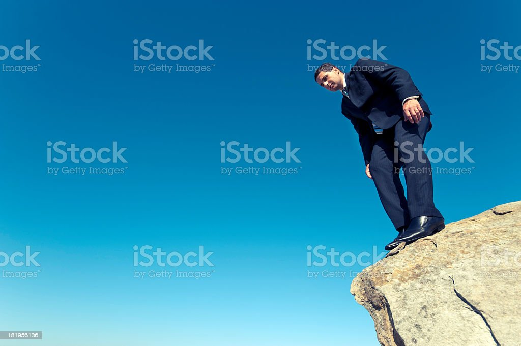 Businessman peering off the edge of a cliff royalty-free stock photo