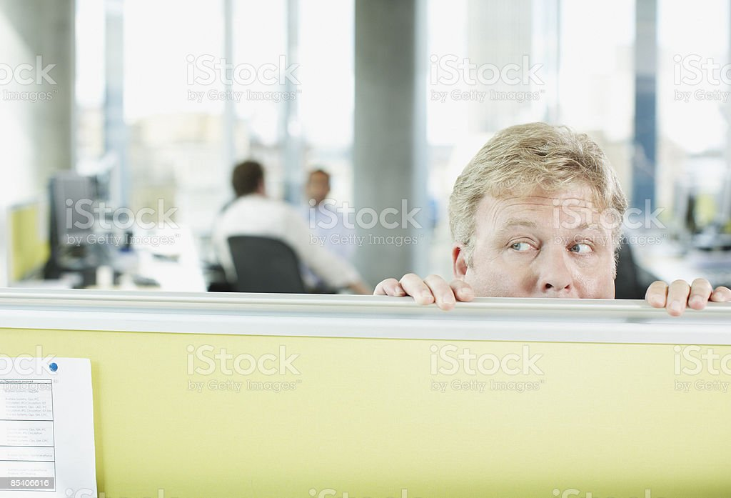 Businessman peering over cubicle wall stock photo