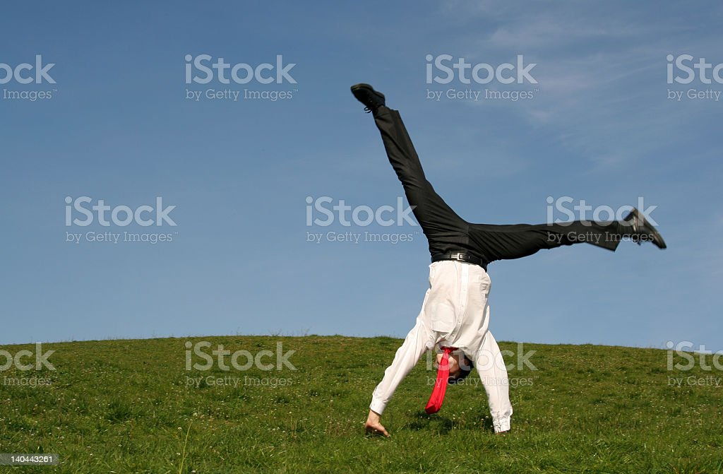 Businessman performing cartwheel in a green field stock photo