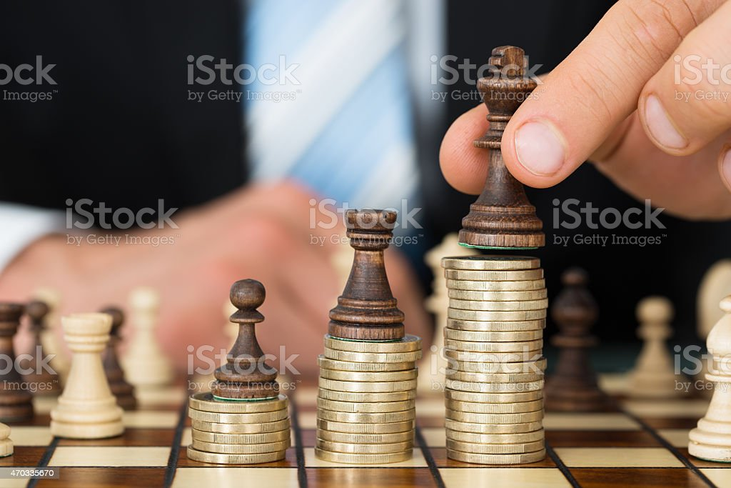 Businessman Placing Chess Pieces On Stacked Coins stock photo